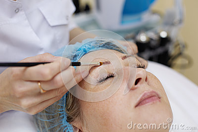 Beautician that works with eyebrow of woman.