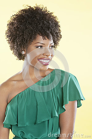 Beautiful African American in an off shoulder dress looking away over colored background