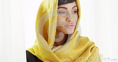 African woman wearing gold head scarf in bright room indoors