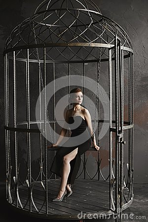 Free Beautiful, And Fashionable Brunette Model Girl In Long Black Dress And Bright Silver Shoes Sits On A Hanging Swing And Posing Royalty Free Stock Photography - 120235587