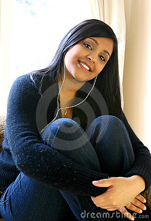 Beautiful Asian female youth listening to her favorite music in