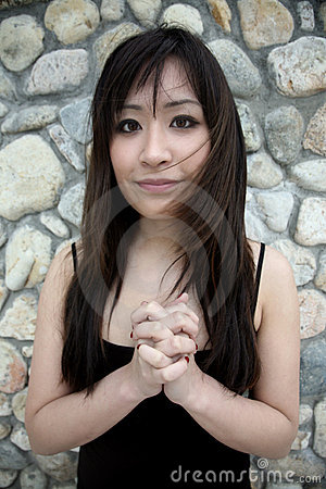 Beautiful Asian girl with hands clasped
