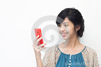 Beautiful asian girl smiling at her smartphone