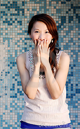 Beautiful Asian lady in front of mosaic and laugh