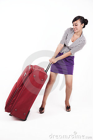 Beautiful Asian woman with heavy suitcase