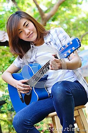 Beautiful asian woman holding Guitar