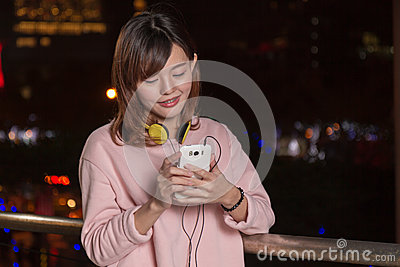 Beautiful Asian woman with smart phone and yellow headphones
