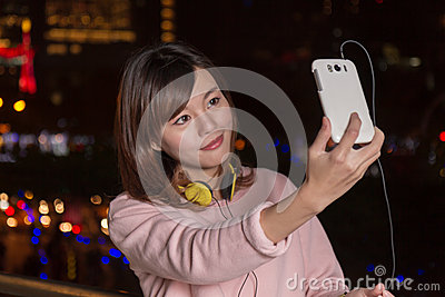 Beautiful Asian woman taking picture with smart phone wearing ye