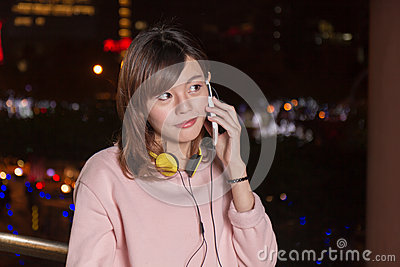 Beautiful Asian woman talking on smart phone and yellow headphon