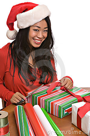 Beautiful Asian woman wraps Christmas presents