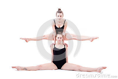 2 beautiful athlete flexible young women siting in split one on top of shoulders of another