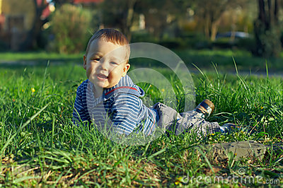 Beautiful baby boy lying on green grass