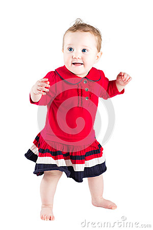 Beautiful baby girl in a red dress making her first steps