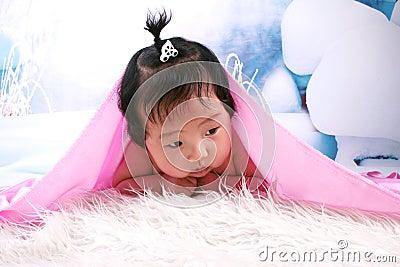 Beautiful baby girl under blanket