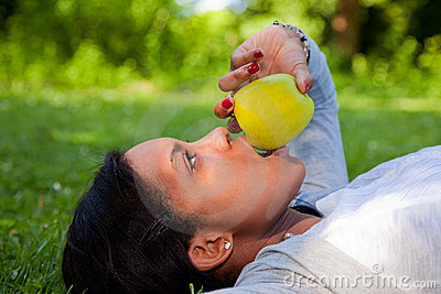 Beautiful black woman  eating an apple