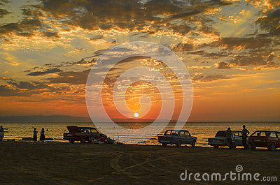 Beautiful blazing sunset landscape at Caspian sea and orange sky above it with awesome sun golden reflection on calm waves as a ba Stock Photo