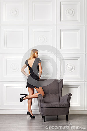 Beautiful blond girl in black dress near armchair