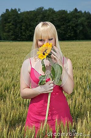 Beautiful blond girl hiding behind a sunflower