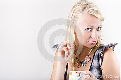 Woman Holding Teabag And Mug In Kitchen