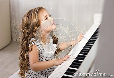 Beautiful Blond Little Girl Playing Piano Stock