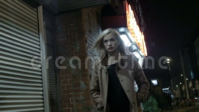 Beautiful blond woman in coat walking alone outdoors at night. Grain. Slow motion. Woman in autumnal coat walking alone outdoors at night, outdoor. Slow motion stock footage