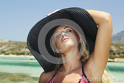 Beautiful blond woman in hat.paradise island