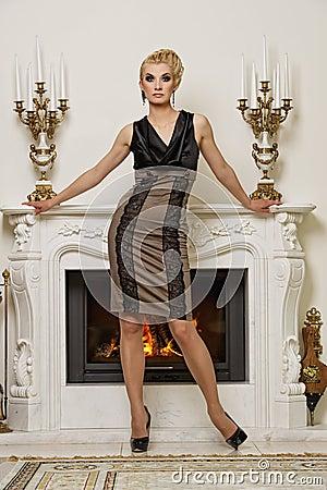 Beautiful blond woman near the fireplace