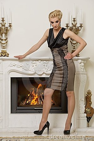 Beautiful blond woman near the fireplace