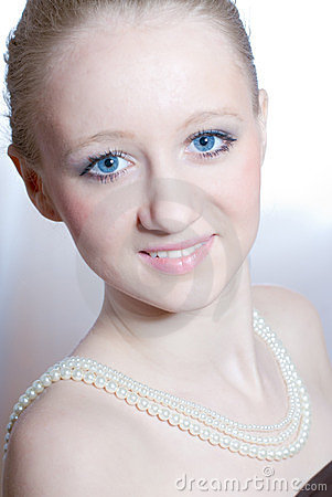 Beautiful blond young woman with pearls necklace