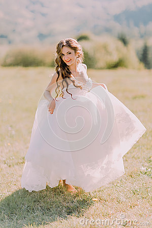 Free Beautiful Blonde Bride In Wedding Dress Runs Across The Field Toward Mountains Royalty Free Stock Image - 70781886