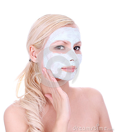 Beautiful blonde girl applying clay mask on face