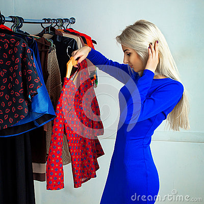Free Beautiful Blonde Girl In Blue Dress Choosing A Shirt In Clothing Stock Photography - 67104322
