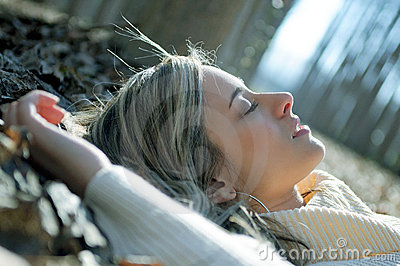 Beautiful blonde girl lying on leaves