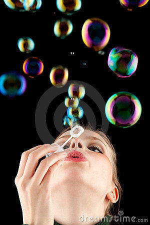 Beautiful blonde girl making colorful soap bubbles
