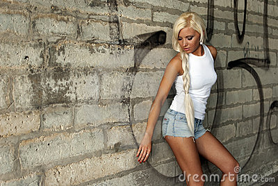 Beautiful blonde girl posing by the wall