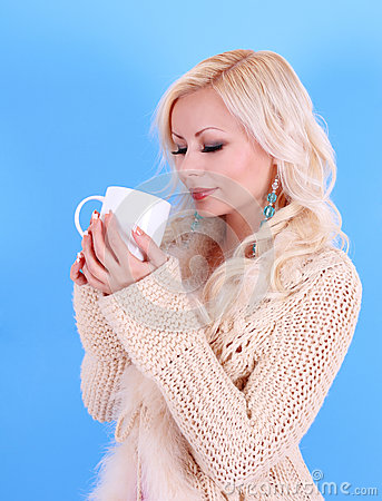 Beautiful blonde girl in pullover with cup of coffee, over blue