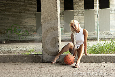 Beautiful blonde girl is sitting with basketball