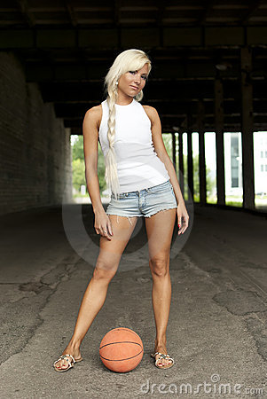 Beautiful blonde girl standing with basketball
