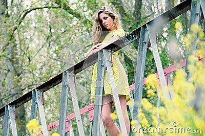 Beautiful blonde girl standing in a rural bridge