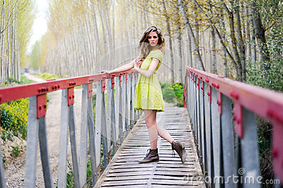 Beautiful blonde girl standing in a rural bridge