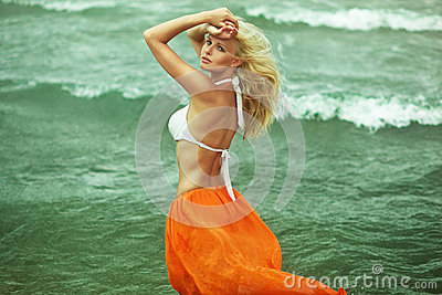 Beautiful blonde girl walking near the sea