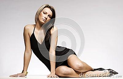 Beautiful blonde girl wearing black mini dress