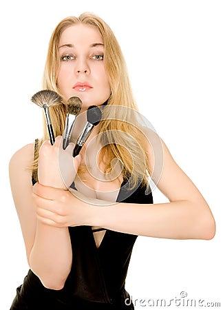 Beautiful blonde holding brushes