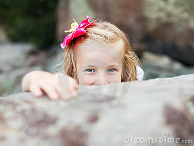Beautiful blonde little girl hides