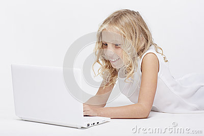 Beautiful blonde little girl in white, computer