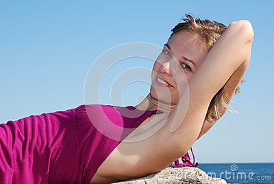 Beautiful blonde lying on the rock