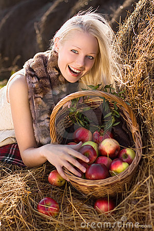 Beautiful blonde smiling woman with many apple