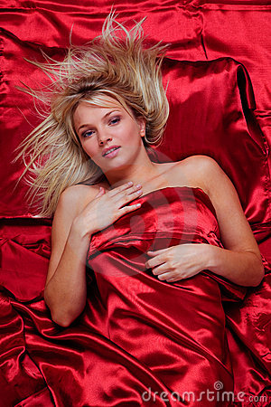 Beautiful blonde woman in a bed of red silk sheets