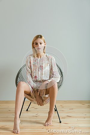 Beautiful blonde woman in dress with floral print sits on a chair on a gray background. Fashion model. Stock Photo