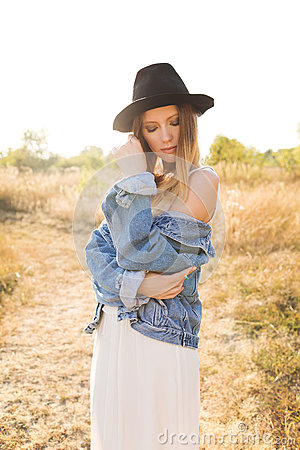 Free Beautiful Blonde Woman In A Long White Dress, Denim Jacket And Hat Posing In The Field. Stock Images - 85794274